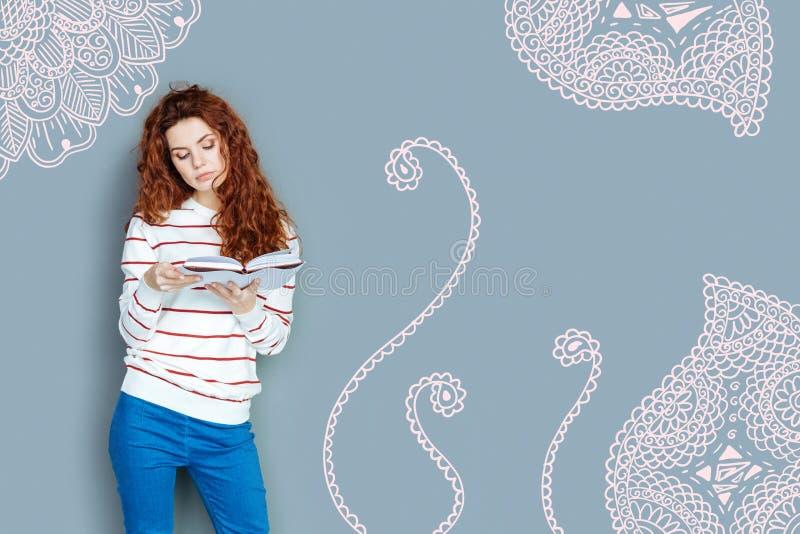 Ήρεμος δάσκαλος που φαίνεται ενδιαφερόμενος διαβάζοντας ένα βιβλίο στοκ φωτογραφία