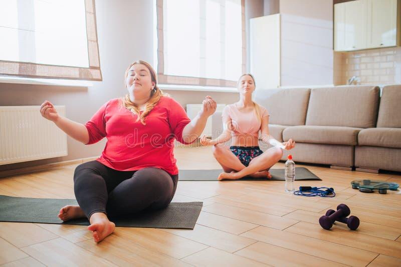 Ήρεμος ειρηνικός νέος λεπτός και συν τα πρότυπα μεγέθους κάθεται στο λωτό θέτει και meditating Μαζί στο καθιστικό Workout για δύο στοκ φωτογραφία