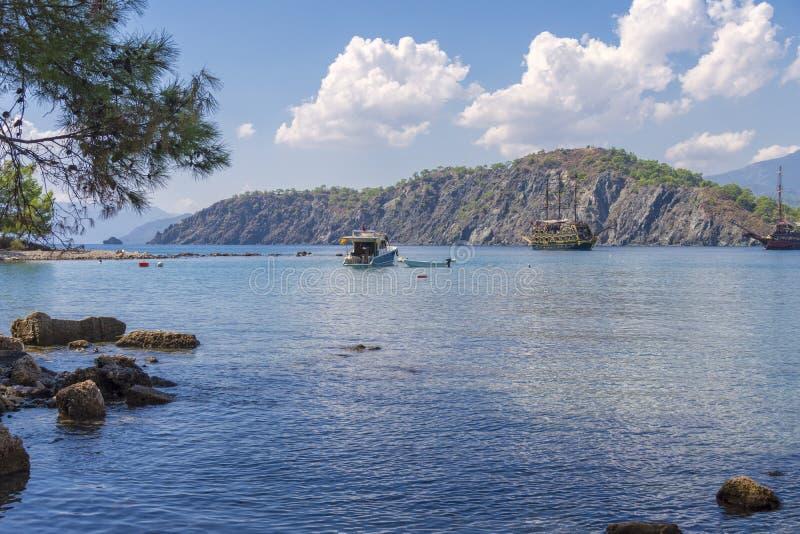 Ήρεμος κόλπος στον τομέα των ιστορικών καταστροφών της πόλης Phaselis, της όμορφης θάλασσας, της πράσινης βλάστησης, των σκαφών κ στοκ εικόνα