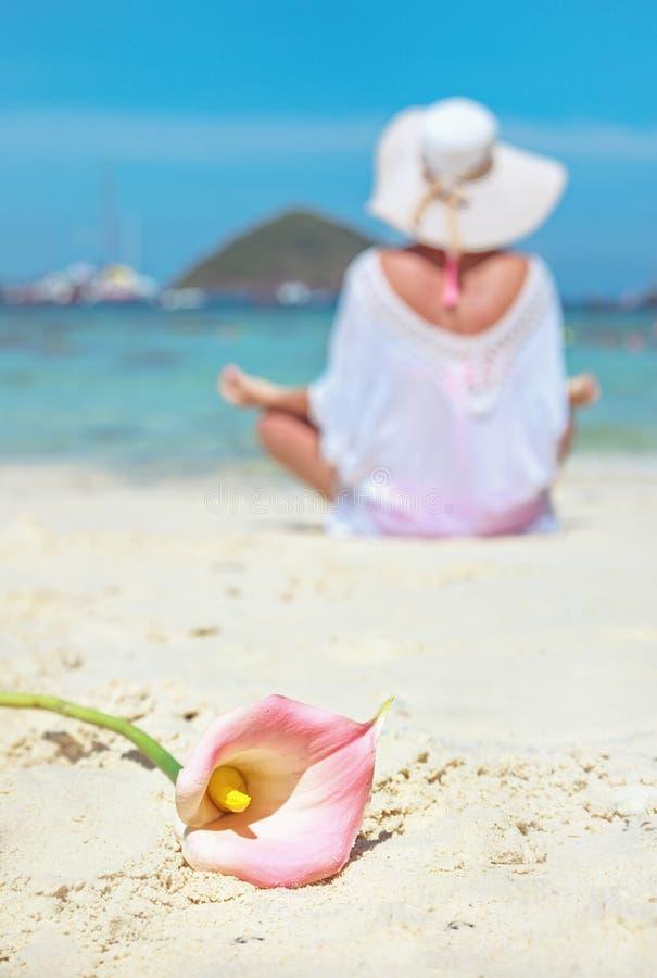 Ήρεμο γυναικείο σε μια παραλία, όμορφο λουλούδι στοκ εικόνες