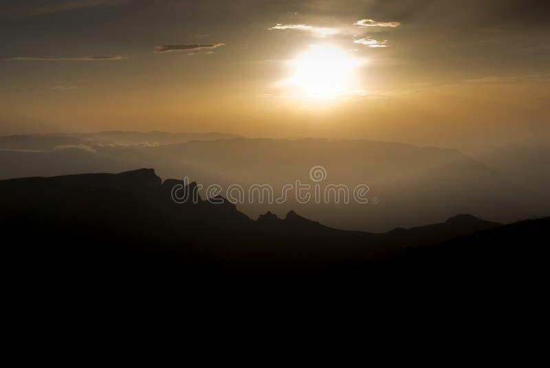 Ήρεμο θερμό ηλιοβασίλεμα επάνω από τα ειρηνικά βουνά στοκ εικόνες