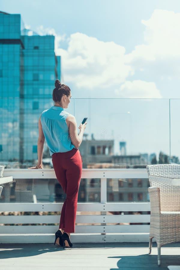 Ήρεμο θηλυκό στέλνοντας μήνυμα στο τηλέφωνο υπαίθριο στοκ εικόνες