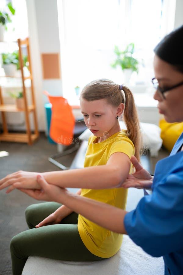 Ήρεμο μεμβρανοειδές μακρυμάλλες παιδί που τραβά τα χέρια και που παρουσιάζει τις δυνατότητες στοκ εικόνες