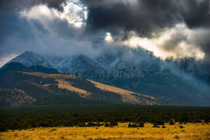 Ήλιος που λάμπει μέσω των σκοτεινών σύννεφων πέρα από τον αμμόλοφο άμμου βουνών στοκ φωτογραφίες