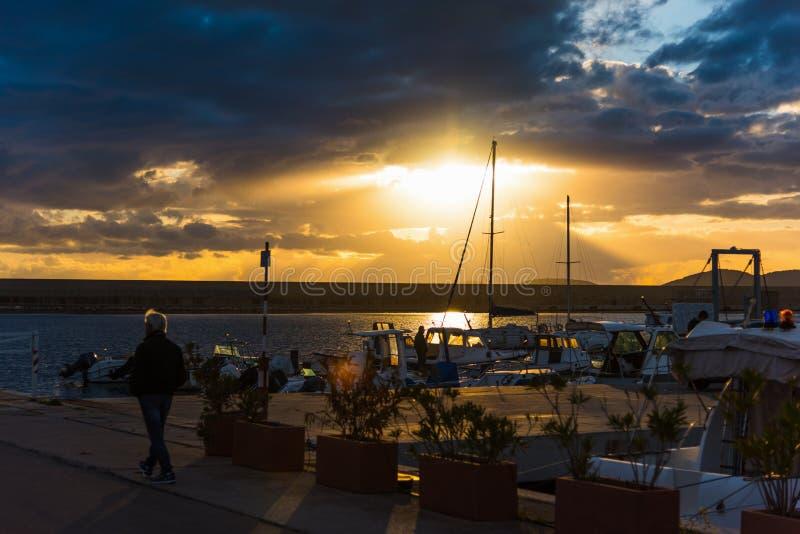 Ήλιος που λάμπει μέσω των σύννεφων πέρα από το λιμάνι Alghero στοκ εικόνες
