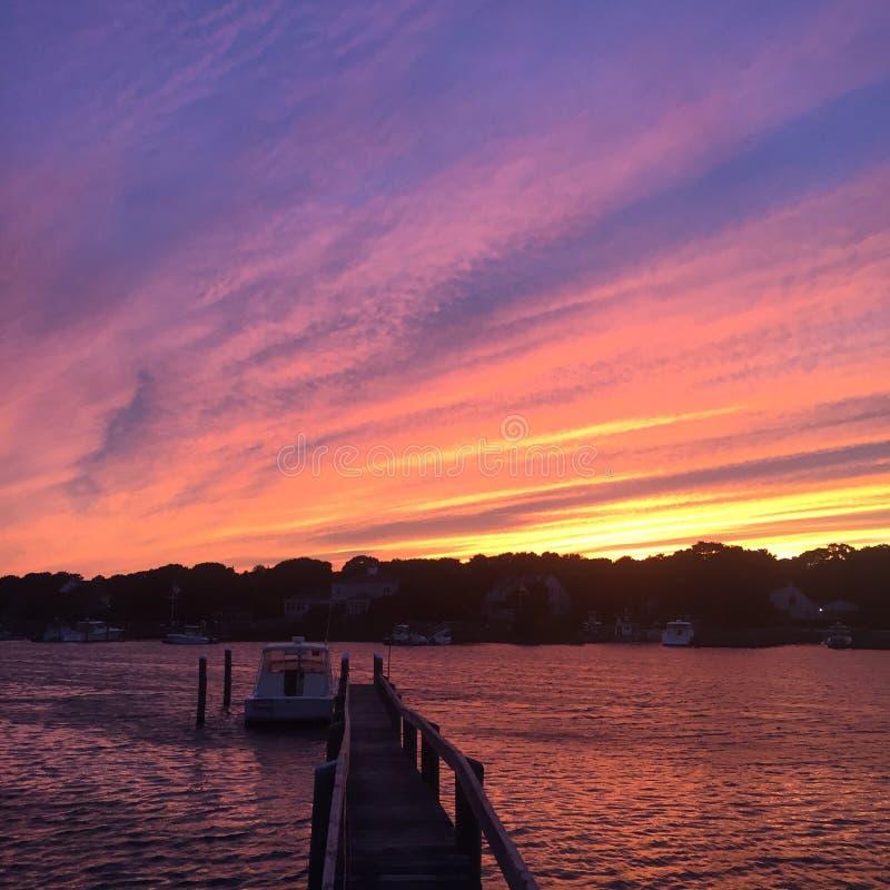 Ήλιος που θέτει πέρα από μια βάρκα το καλοκαίρι στοκ φωτογραφία