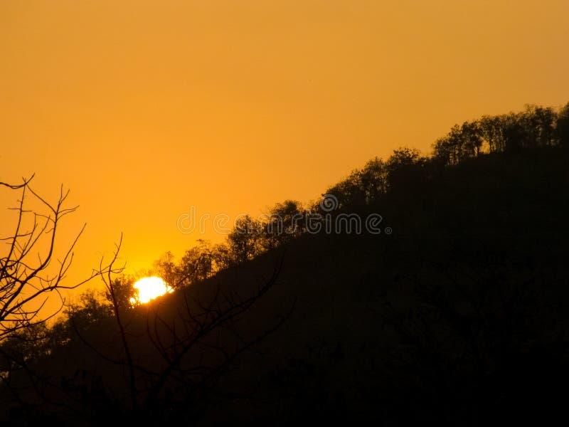Ήλιος που θέτει πίσω από το βουνό στοκ φωτογραφίες