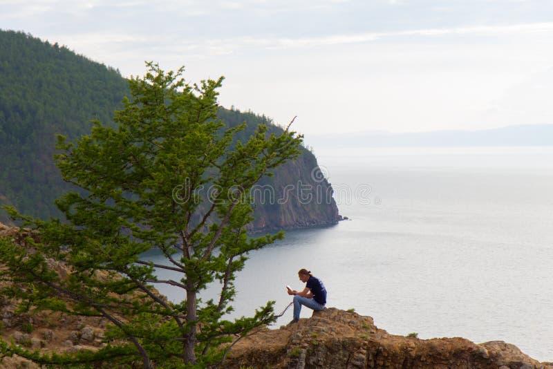λίμνη 08 Baikal του 2014: Άτομο RussiaYoung που καλαμώνει ένα βιβλίο στο νησί Olkhon στη λίμνη Baikal στοκ φωτογραφία με δικαίωμα ελεύθερης χρήσης