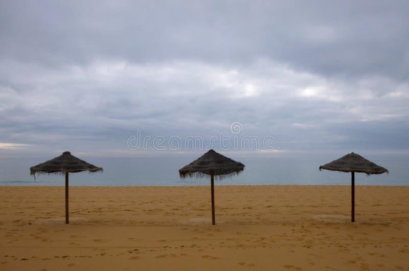 """Ίνα ραφίας τρία parasols στην αμμώδη παραλία με Ï""""Î¿ άσχημο καιρό στοκ φωτογραφία με δικαίωμα ελεύθερης χρήσης"""