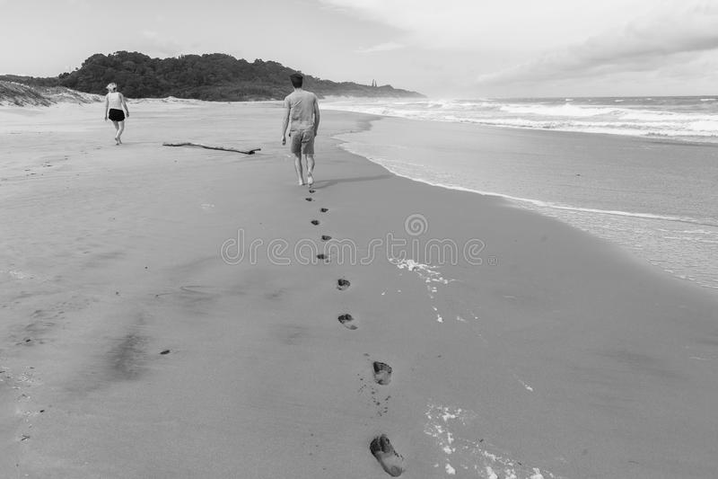 Ίχνη αγοριών κοριτσιών που περπατούν τον ωκεάνιο τρύγο παραλιών στοκ φωτογραφίες