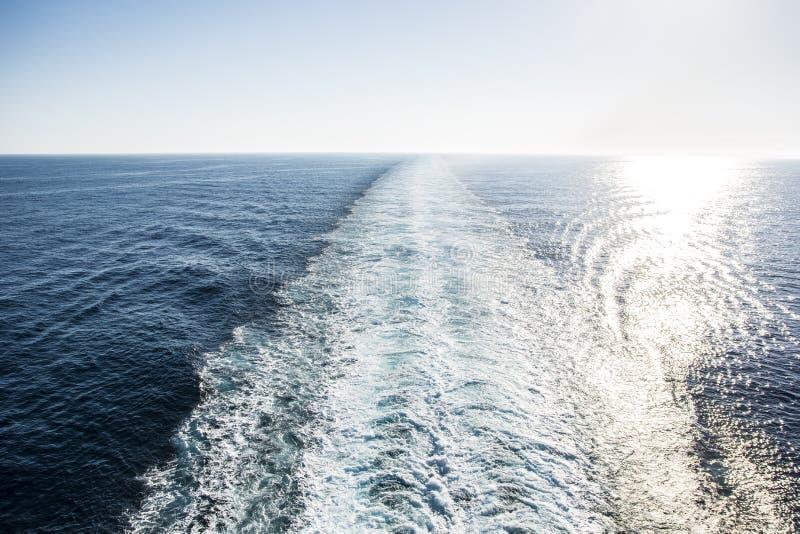 Ίχνη ενός κρουαζιερόπλοιου κατά τη διάρκεια της σαφούς μπλε ημέρας στοκ φωτογραφία