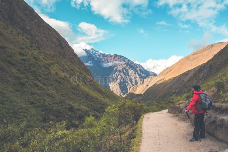 Ίχνος Inca, Περού: Στις 11 Αυγούστου 2018: Ένας θηλυκός οδοιπόρος παίρνει ένα υπόλοιπο και φαίνεται η όμορφη άποψη πίσω από την Ε στοκ φωτογραφίες