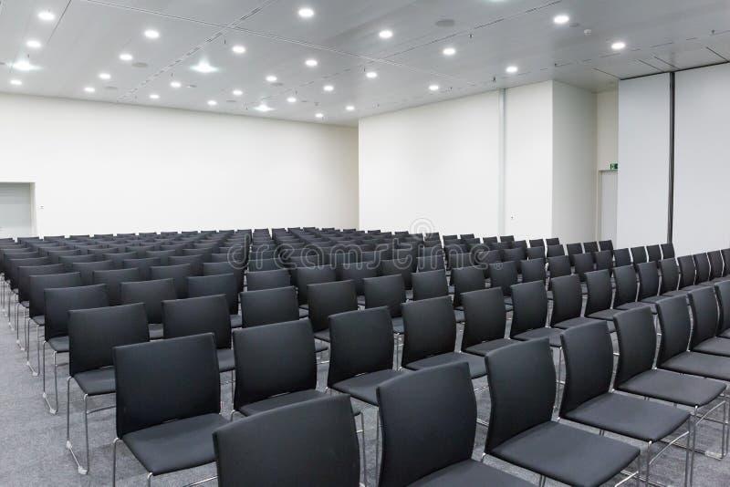 Αίθουσα διασκέψεων και συνεδριάσεων με τις σειρές των μαύρων εδρών στοκ εικόνα