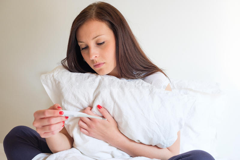 Αίσθημα γυναικών που πιέζεται και λυπημένο μετά από να εξετάσει τη δοκιμή εγκυμοσύνης στοκ εικόνες