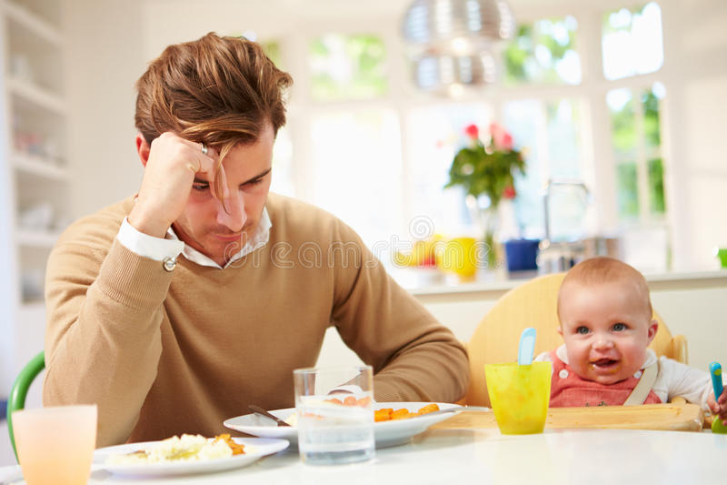 Αίσθημα πατέρων που πιέζεται σε Mealtime του μωρού στοκ φωτογραφίες