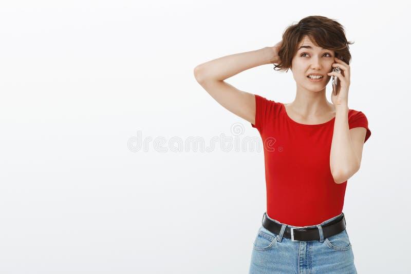 Αβέβαιο μπερδεμένο χαριτωμένο κορίτσι που κάνει τη γρατσουνιά αυτιών smartphone λαβής τηλεφωνημάτων διαταγής την επικεφαλής αβέβα στοκ φωτογραφία