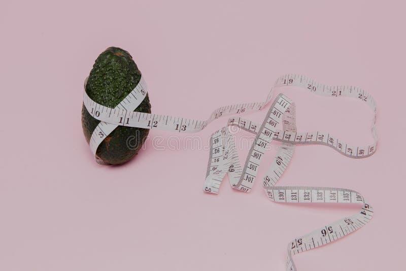 Αβοκάντο με το μετρητή στο ρόδινο υπόβαθρο Έννοια τροφίμων διατροφής Συστατικό τροφίμων διατροφής στοκ εικόνα