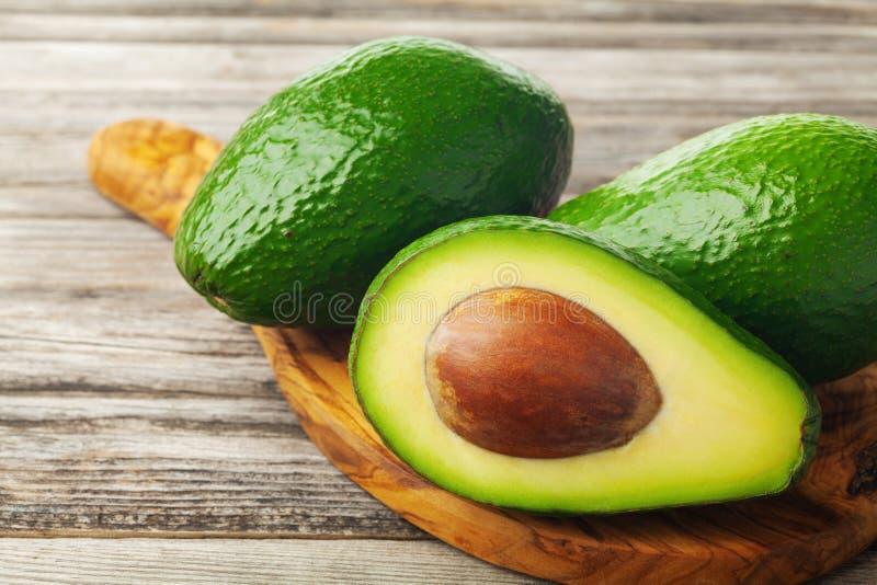 Αβοκάντο μισό και ολόκληρο στον ξύλινο πίνακα Υγιή διαιτητικά φρούτα στοκ εικόνες