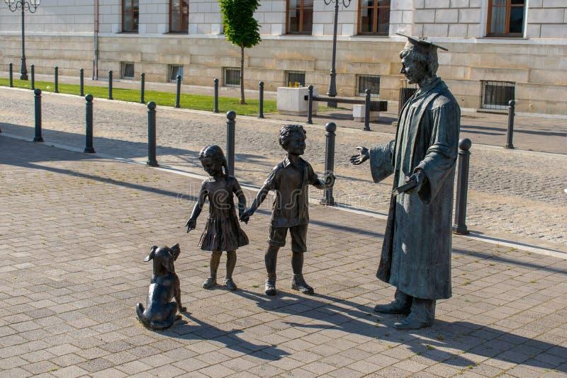 Αγάλματα των παιδιών που παίζουν με το δάσκαλό τους στοκ εικόνα