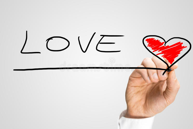 Αγάπη λέξης γραψίματος ατόμων με μια κόκκινη καρδιά στοκ φωτογραφία με δικαίωμα ελεύθερης χρήσης
