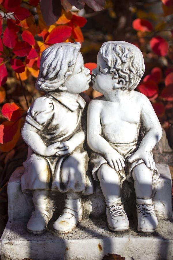 Αγάπη βαλεντίνων, άγαλμα φιλήματος και κόκκινα φύλλα στοκ εικόνες