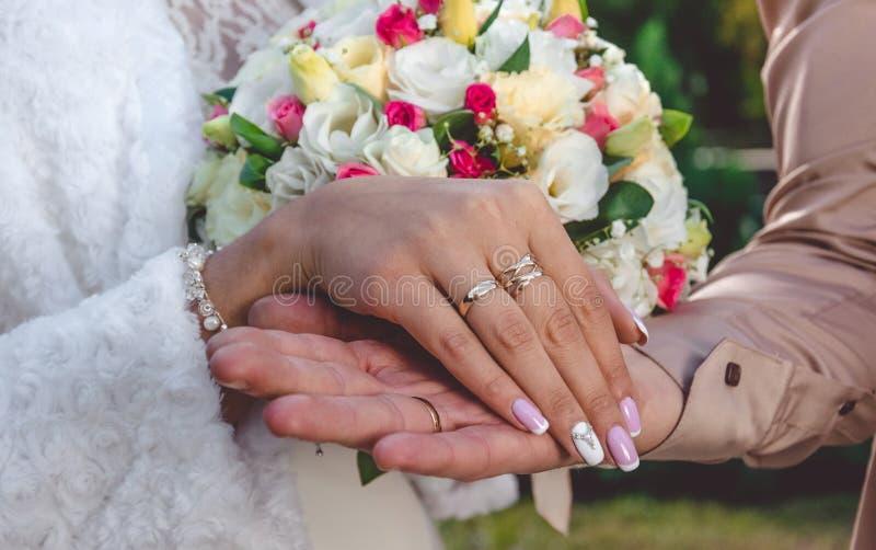 Αγάπη και τρυφερότητα Χέρι νυφών ` s με το γαμήλιο δαχτυλίδι στοκ εικόνα