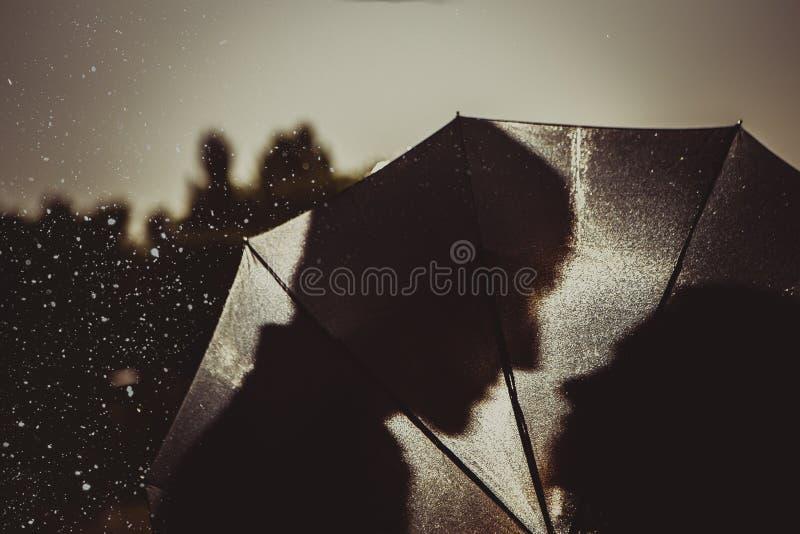 Αγάπη στη βροχή/τη σκιαγραφία του φιλήματος του ζεύγους κάτω από την ομπρέλα στοκ φωτογραφία με δικαίωμα ελεύθερης χρήσης