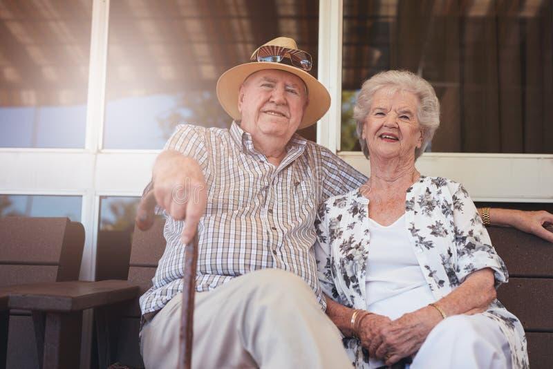 Αγάπη της αποσυρμένης χαλάρωσης ζευγών σε έναν πάγκο έξω από το σπίτι τους στοκ εικόνες