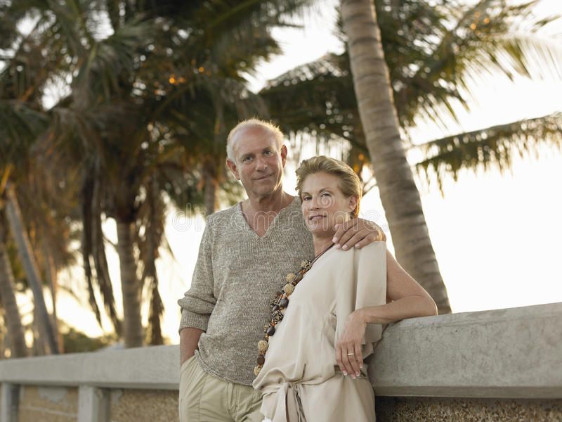 Αγάπη του ανώτερου ζεύγους που κλίνει ενάντια στον τοίχο στην παραλία στοκ φωτογραφία με δικαίωμα ελεύθερης χρήσης