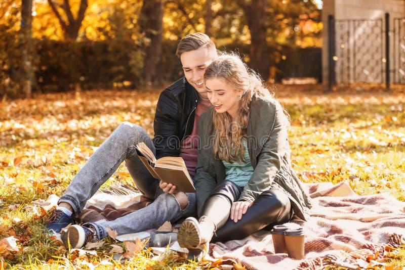 Αγάπη του νέου βιβλίου ανάγνωσης ζευγών στο καρό στο πάρκο φθινοπώρου στοκ εικόνα