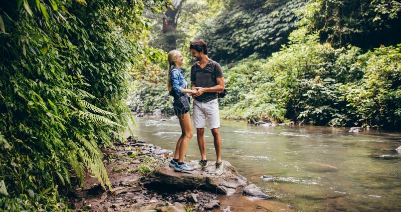 Αγάπη του νέου ζεύγους που υπερασπίζεται το ρεύμα βουνών στοκ φωτογραφίες