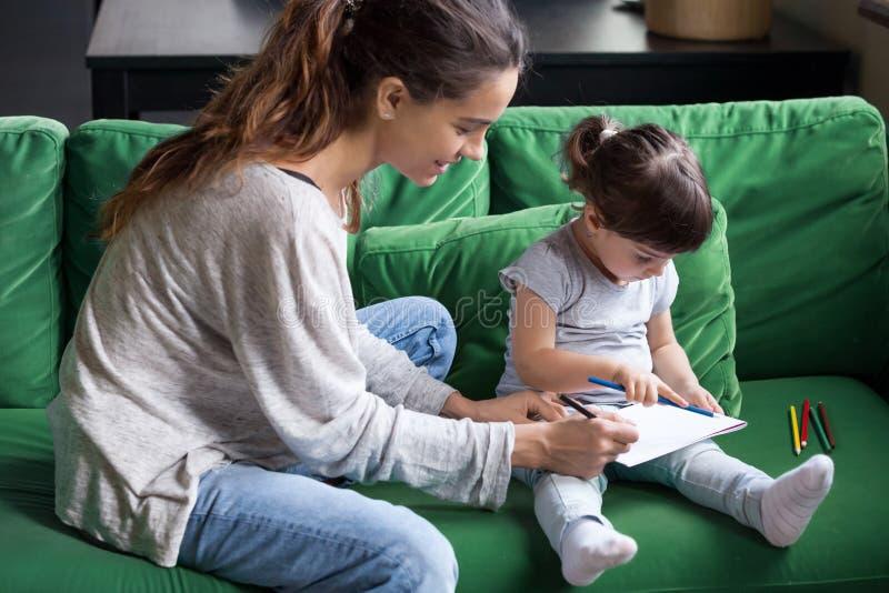 Αγάπη του νέου χρωματισμού μητέρων με λίγη κόρη στοκ εικόνες