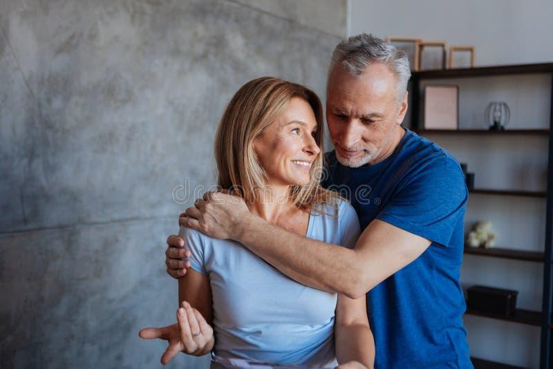 Αγάπη του φροντίζοντας συζύγου που αγκαλιάζει την ακτινοβολώντας ελκυστική σύζυγό του στοκ φωτογραφίες