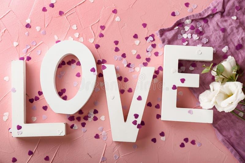 ΑΓΑΠΗ λέξης με το κομφετί και τα λουλούδια στο υπόβαθρο χρώματος στοκ εικόνες
