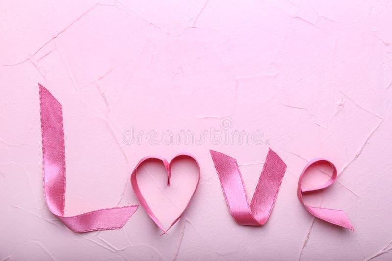 ΑΓΑΠΗ λέξης φιαγμένη από ρόδινη κορδέλλα στον πίνακα χρώματος στοκ φωτογραφία με δικαίωμα ελεύθερης χρήσης