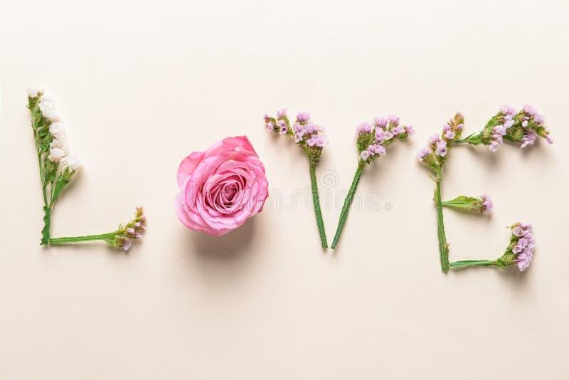 ΑΓΑΠΗ λέξης φιαγμένη από όμορφα λουλούδια στο ελαφρύ υπόβαθρο στοκ εικόνα με δικαίωμα ελεύθερης χρήσης