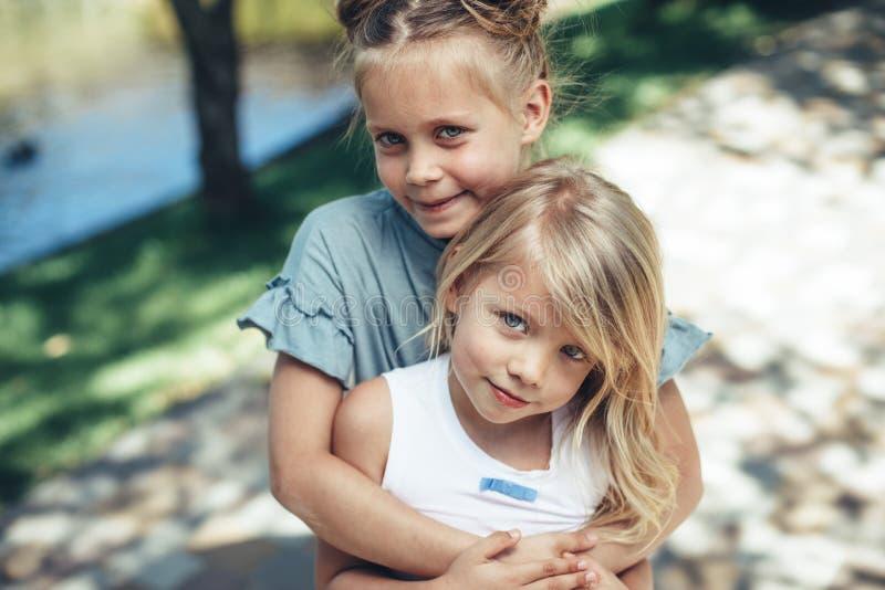 Αγαπώντας αδελφές που αγκαλιάζουν στην οδό στοκ φωτογραφίες