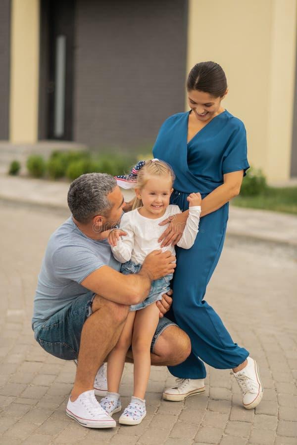 Αγαπώντας γονείς που αγκαλιάζουν την ακτινοβολώντας χαριτωμένη κόρη τους στοκ φωτογραφία με δικαίωμα ελεύθερης χρήσης