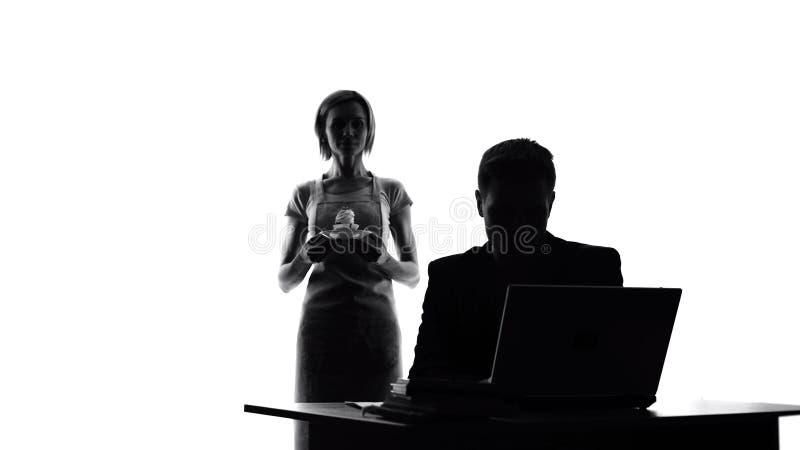 Αγαπώντας γυναίκα στην ποδιά με το κέικ που εξετάζει τον εργαζόμενο σύζυγο, νόστιμη έκπληξη στοκ εικόνες