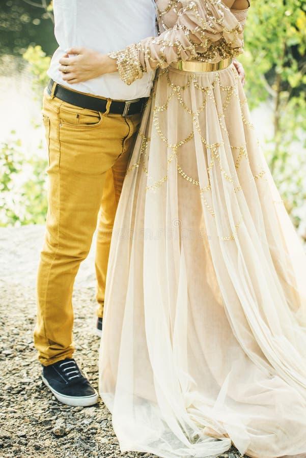 Αγαπώντας ζεύγος που αγκαλιάζει στο δασικό μπεζ φόρεμα στοκ φωτογραφία με δικαίωμα ελεύθερης χρήσης