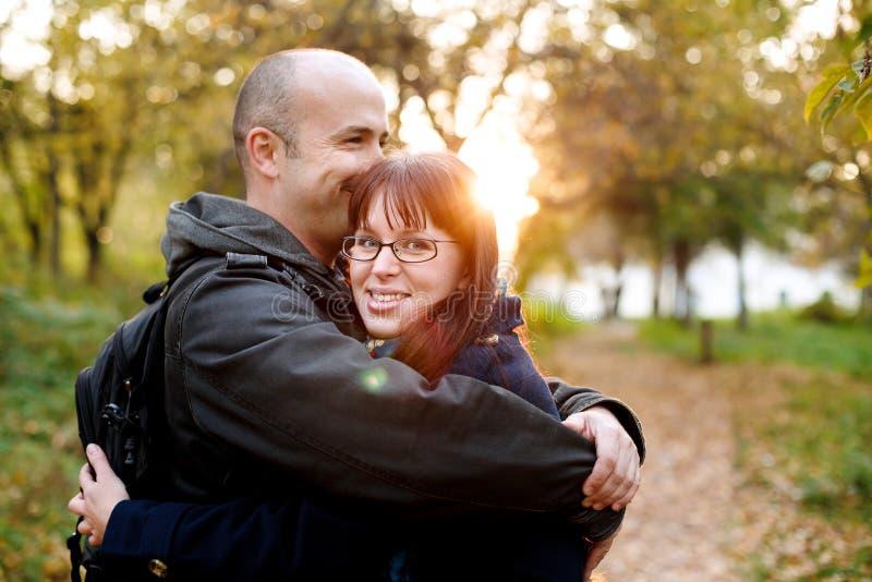 Αγαπώντας ζεύγος που αγκαλιάζει στο πάρκο το θερμό φθινόπωρο στοκ εικόνες