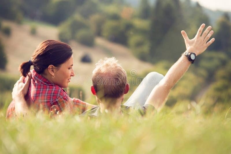 Αγαπώντας ζεύγος που βρίσκεται στην πράσινη χλόη στο λιβάδι στοκ εικόνα με δικαίωμα ελεύθερης χρήσης