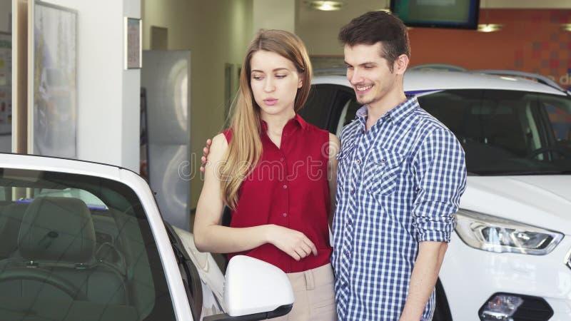 Αγαπώντας ζεύγος που εξετάζει νέο έναν μετατρέψιμο για την πώληση στον αντιπρόσωπο στοκ φωτογραφία με δικαίωμα ελεύθερης χρήσης