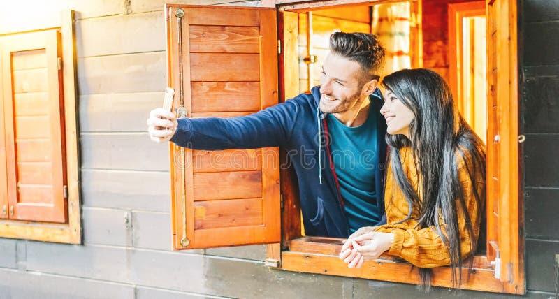 Αγαπώντας ζεύγος που παίρνει ένα selfie έξω από το παράθυρο του ξύλινου σπιτιού τους - νέοι εραστές που παίρνουν τις εικόνες με τ στοκ εικόνες