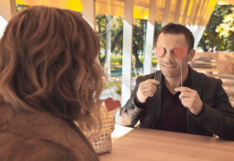 Αγαπώντας ζεύγος στο εστιατόριο με την κόκκινη καρδιά στοκ εικόνες