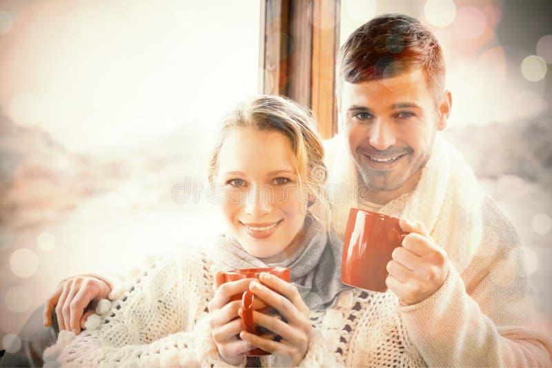 Αγαπώντας ζεύγος στο χειμερινό ιματισμό με τα φλυτζάνια καφέ ενάντια στο παράθυρο απεικόνιση αποθεμάτων