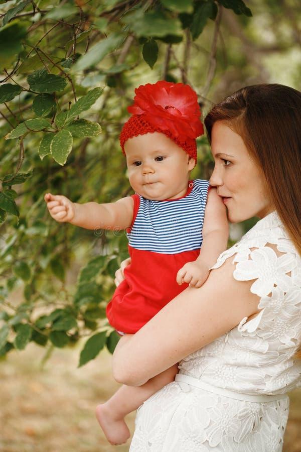 Αγαπώντας νέα εκμετάλλευση και φίλημα μητέρων του μωρού της στοκ φωτογραφία