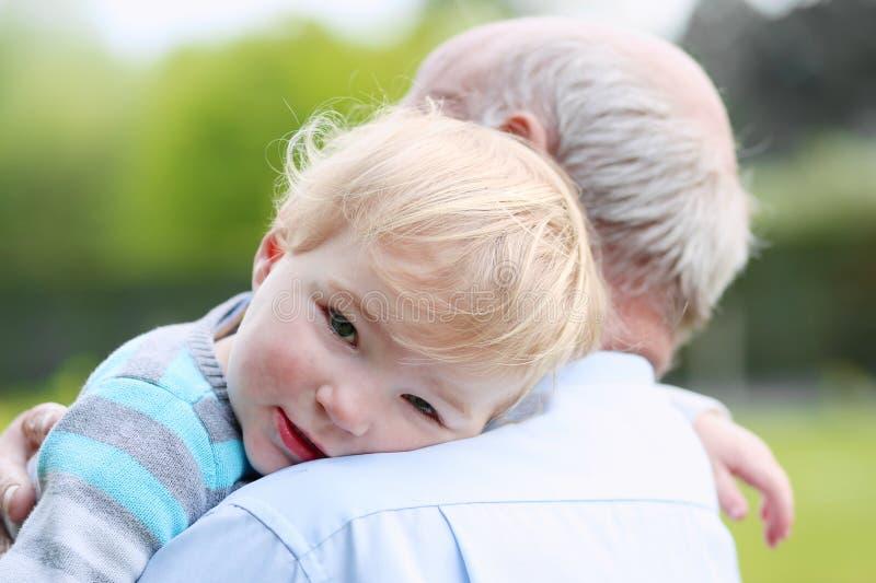 Αγαπώντας παππούς που κρατά το μικρό εγγόνι του στοκ φωτογραφίες