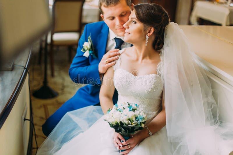 Αγαπώντας το μοντέρνο ντυμένο νεόνυμφο που φιλά ήπια τη νέα σύζυγό του στο όμορφο άσπρο φόρεμα στοκ εικόνες