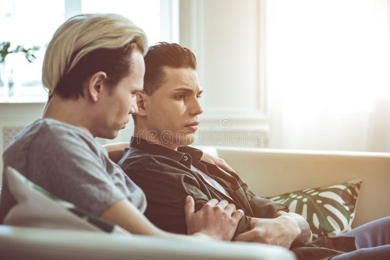 Αγαπώντας φίλος σχετικά με το βραχίονα του λυπημένου νεαρού άνδρα στοκ εικόνα με δικαίωμα ελεύθερης χρήσης